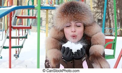 Woman blowing in the snow twice - Woman in fur cap, blowing...