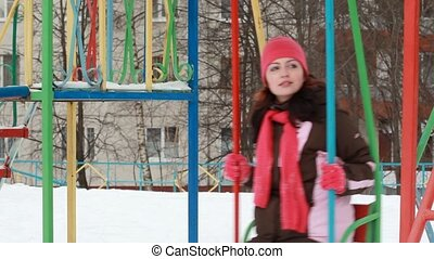 Woman on swings on playground - Woman in pink cap and scarf...