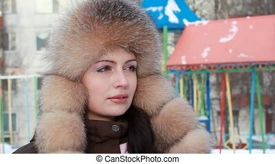 Woman looks and smiling against background of playground -...