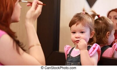 Woman doing makeup and daughter sitting near