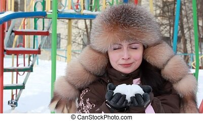 Woman blowing in snow on hands - Woman in fur cap, blowing...