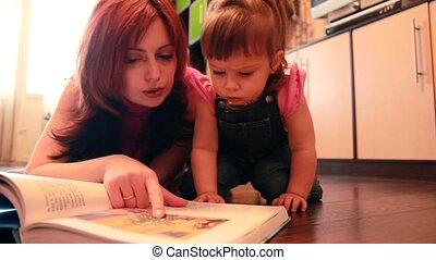 Mom and baby girl are lying on the floor considering book -...