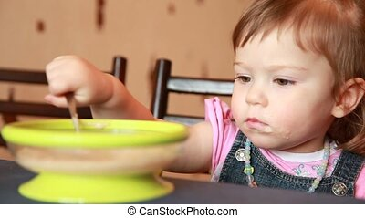 Baby girl is eating porridge from a green plate using spoon