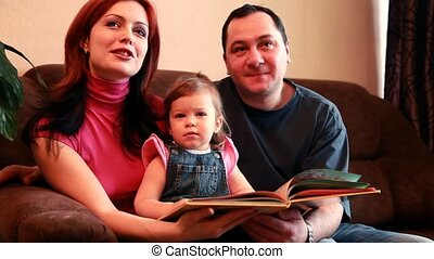 Parents and baby girl are watching TV, then in a book