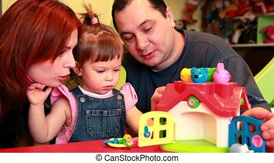 Parents watching how their baby are playing with doll-house