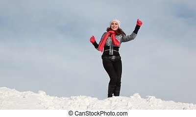 The woman in red scarf, is dancing on the slope which is fully covered of snow