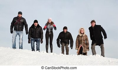 Group of young people are laughing on slope with snow in...