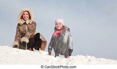 The women are sitting and throwing snow