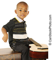Tiny Guitarist - A handsome preschooler happily playing...