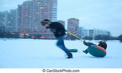 The adult boy holds a sleds behind his back and spin it around