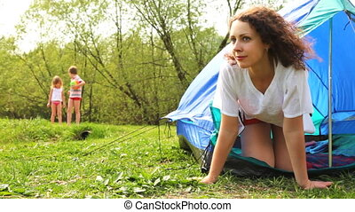 Woman looks out from tent on two kids, then they come and pull cord at forest