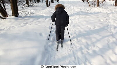 Young boy escapes on skis from camera by day in winter woods