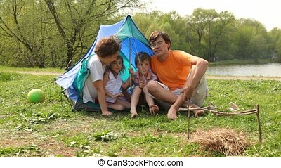 Family near tent and ball in summer park