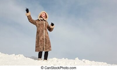 The woman is dancing on the slope which is fully covered of...