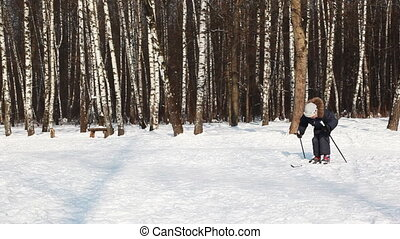 Young boy glides on skis, pushing sticks by day in winter...