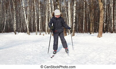 Young boy turns on skis around its axis by day in winter...