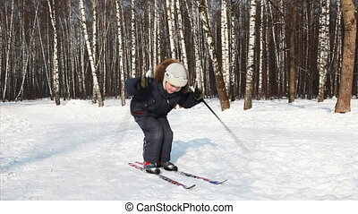 Young boy bounces on skis, pushing off sticks by day in...