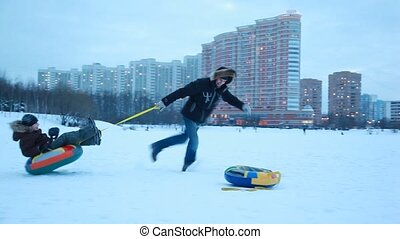 The adult boy spins the sled around in the winter