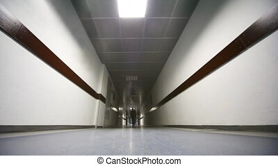 Businessman comes through wide corridor in office at camera,...