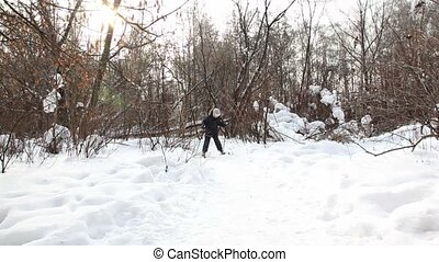 Young boy runs on skis to camera by day in winter woods