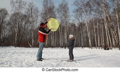 Father with boy start chinese lantern rises in sky