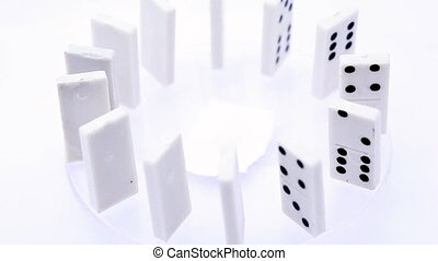 Dominoes with black dots stand vertically aligned in circle...
