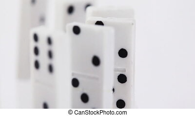 Dominoes with black dots stand vertically and pass consistently in front of camera