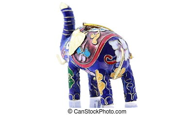 Souvenir elephant painted in oriental style stands on rotating glass