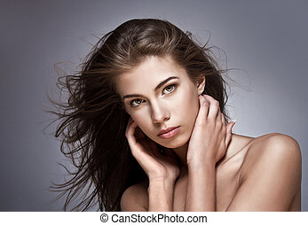 Beautiful woman with fluttering hair On dark background