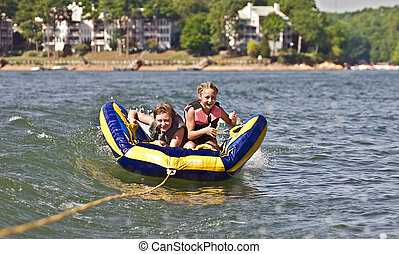 Children Tubing Behind a Boat - A young boy and girl riding...