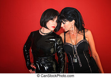 Two Sexy Dominatrix Women Pose on Red - Two dominatrix women...