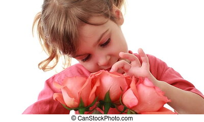 Little girl touches beautiful pink roses in bouquet and says something