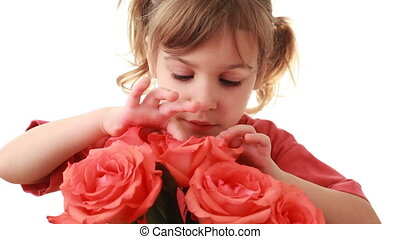 Nice little girl looks inside pink rose in beautiful bouquet