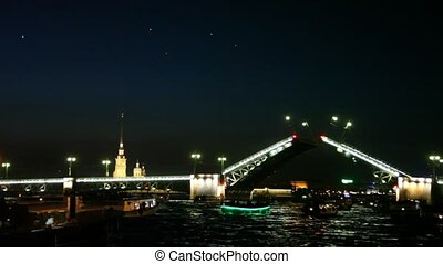 Raised drawbridge at night on Neva illuminated with lights