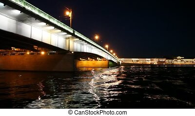 Camera moves under lighted Liteyny Bridge standing on Neva