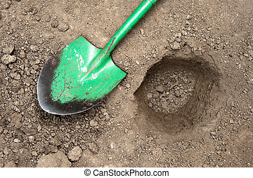 Dug hole and shovel - A hole in the dirt with shovel on...