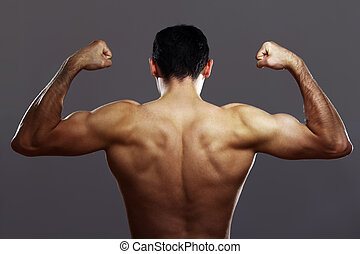 Young muscular guy over gray background