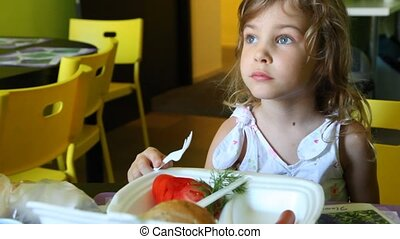 Girl smiling and watches TV while eating at table - girl...