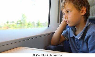 Boy sits and looks out of window trains during movement has...