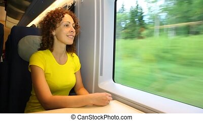 Woman sits and smiling in train near window during movement...