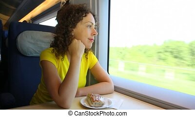 Woman sits in train near window during movement at table -...