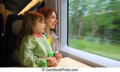 Mother with daughter ride in speeding train and look at...