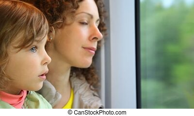Closeup mother with daughter ride in speeding train and look...