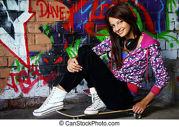 Beautiful teenager girl with headphones sitting on...