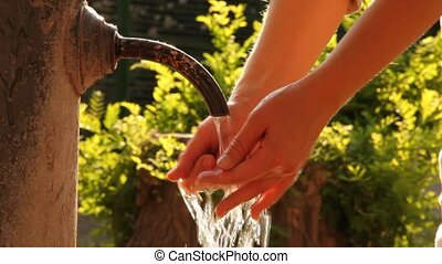 Woman washes hands in stream of water from old rusty tap -...