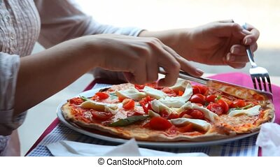 Hands of woman cut pizza with knife and fork