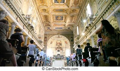 Tourists are present on church service at Papal Basilica of Saint Mary Major
