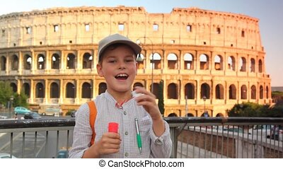 Boy blow soap bubbles on pedestrian crossing on background of Colosseum