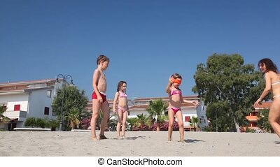Woman in bikini with children play hide and seek on beach -...