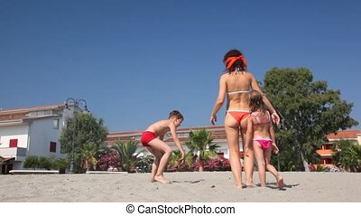 Blindfold woman with boy and gir play hide and seek on beach...